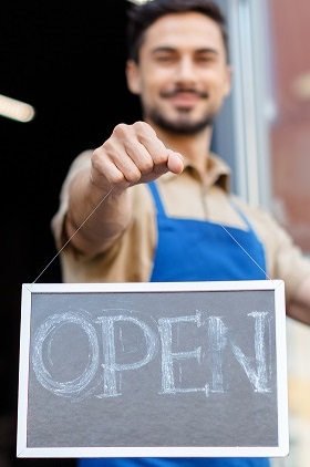 close-up view of smiling male business owner holding open sign